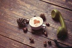 Tazza di caffè con forma del cuore ed il microtelefono verde fotografia stock
