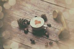 Tazza di caffè con forma del cuore ed il microtelefono verde immagine stock