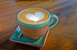 Tazza di caffè, con forma del cuore su fondo di legno Fotografie Stock