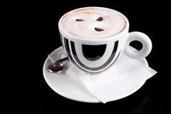Tazza di caffè con gomma piuma e fagioli sulla parte superiore Fotografia Stock