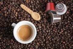 Tazza di caffè con i baccelli Fotografia Stock