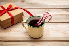 Tazza di caffè con i bastoncini di zucchero e un contenitore di regalo con il nastro rosso su fondo di legno, spazio della copia immagine stock
