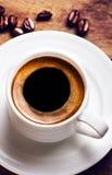 Tazza di caffè con i chicchi di caffè arrostiti su fondo di legno, clos Fotografie Stock