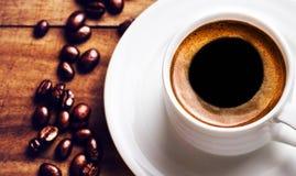 Tazza di caffè con i chicchi di caffè arrostiti su fondo di legno, clos Immagini Stock