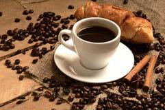 Tazza di caffè con i chicchi di caffè croissant, cannella su insaccamento e fotografia stock