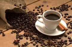 Tazza di caffè con i chicchi di caffè croissant, cannella su insaccamento e legno immagini stock libere da diritti