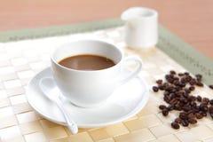 Tazza di caffè con i chicchi di caffè ed il contenitore dello zucchero fotografia stock