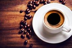 Tazza di caffè con i chicchi di caffè su fondo di legno con copyspac Fotografie Stock