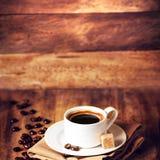 Tazza di caffè con i chicchi di caffè su un bello BAC di legno di marrone Fotografia Stock Libera da Diritti