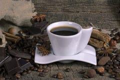 Tazza di caffè con i chicchi, il cioccolato e le spezie di caffè Immagini Stock