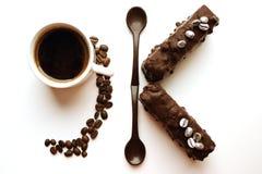 Tazza di caffè con i dessert, i cucchiai del cioccolato e il formin 9K, toni dei chicchi di caffè di seppia fotografie stock