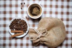 Tazza di caffè con i fagioli e la vista superiore del sacco Immagini Stock
