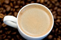 Tazza di caffè con i fagioli sotto la tazza Fotografia Stock Libera da Diritti