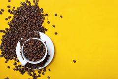 Tazza di caffè con i fagioli su fondo giallo Immagine Stock