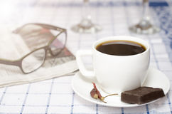 Tazza di caffè con i peperoncini rossi e cioccolato, vetri e giornale Immagine Stock