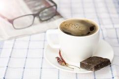 Tazza di caffè con i peperoncini rossi ed il cioccolato Fotografia Stock