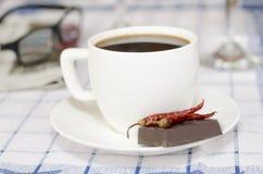 Tazza di caffè con i peperoncini rossi ed il cioccolato Fotografia Stock Libera da Diritti