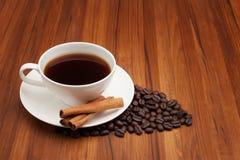 Tazza di caffè con il bastone di cannella sulla tavola di legno Fotografie Stock