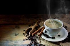Tazza di caffè con il bastone di cannella sulla tavola di legno Fotografia Stock