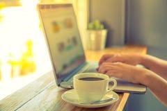 Tazza di caffè con il computer portatile (effetto d'annata elaborato immagine filtrato ) fotografia stock libera da diritti