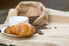 Tazza di caffè con il croissant ed il fagiolo pronti per la prima colazione Fotografie Stock Libere da Diritti