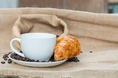Tazza di caffè con il croissant ed il fagiolo sulla Tabella Immagine Stock