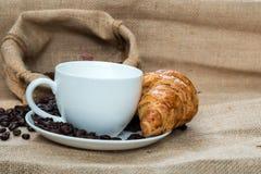 Tazza di caffè con il croissant ed il fagiolo sulla Tabella Fotografie Stock Libere da Diritti