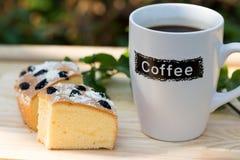 Tazza di caffè con il dolce del burro dell'uva passa fotografie stock libere da diritti