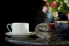 Tazza di caffè con il fiore ed il giornale Fotografia Stock