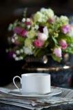 Tazza di caffè con il fiore ed il giornale Immagini Stock