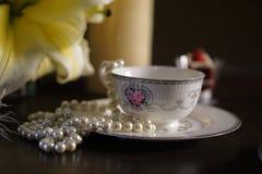 Tazza di caffè con il giglio del fiore ed i gioielli 002 immagine stock libera da diritti
