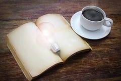 Tazza di caffè con il libro e la lampadina Immagine Stock