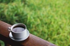 Tazza di caffè con il piattino, sul pannello di legno con il fondo del prato inglese dell'erba verde di defocus Fotografia Stock