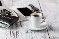 Tazza di caffè con il portafoglio del cuoio e del telefono sulla tavola Fotografia Stock Libera da Diritti