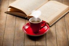 Tazza di caffè con il vapore ed il libro aperto di forma del cuore Fotografia Stock Libera da Diritti