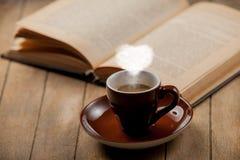 Tazza di caffè con il vapore ed il libro aperto di forma del cuore Fotografia Stock