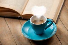 Tazza di caffè con il vapore ed il libro aperto di forma del cuore Immagini Stock