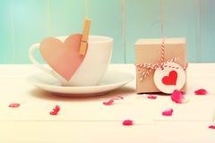 Tazza di caffè con l'etichetta del cuore e un piccolo giftbox Immagine Stock