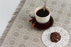 Tazza di caffè con la caramella gommosa e molle del cioccolato e della cannella sulla stuoia contro la tovaglia monocromatica con Fotografia Stock