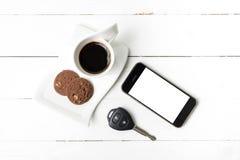 Tazza di caffè con la chiave del biscotto, del telefono e dell'automobile Fotografie Stock Libere da Diritti