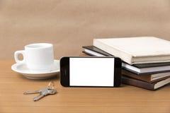Tazza di caffè con la chiave del telefono e la pila di libro Fotografia Stock