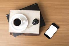 Tazza di caffè con la chiave dell'automobile del telefono e la pila di libro Immagine Stock Libera da Diritti