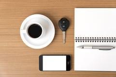 Tazza di caffè con la chiave ed il blocco note dell'automobile del telefono Fotografia Stock