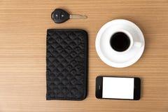 Tazza di caffè con la chiave ed il portafoglio dell'automobile del telefono Immagine Stock