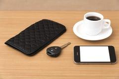 Tazza di caffè con la chiave ed il portafoglio dell'automobile del telefono Fotografia Stock