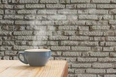 Tazza di caffè con la corrente del vapore contro il backgr bianco del muro di mattoni immagini stock libere da diritti