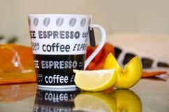 Tazza di caffè con la fetta del limone Immagini Stock