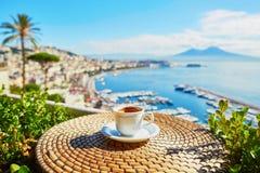 Tazza di caffè con la vista sul supporto di Vesuvio a Napoli fotografia stock