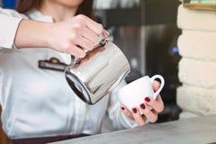 Tazza di caffè con latte in mano del ` s della donna Fotografia Stock