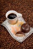 Tazza di caffè con le caramelle sulla priorità bassa dei fagioli Fotografia Stock Libera da Diritti